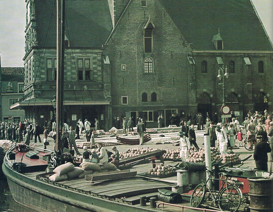 "Loading cheese into 'Catharina Elisabeth' at the Alkmaar Kaasmarkt. Bottom right, in the steering position, you can see the horizontal ship's wheel, and ""M Verwer Zanstreek-Alkmaar"""