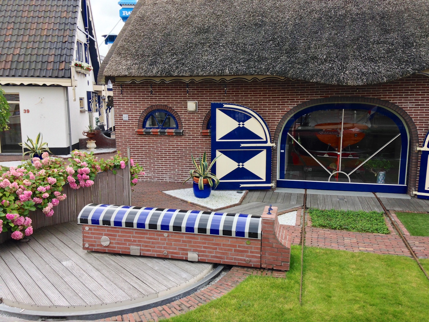 Scenic: thatched houses with sophisticated garage for their boat - but I can't imagine what the turntable is for.