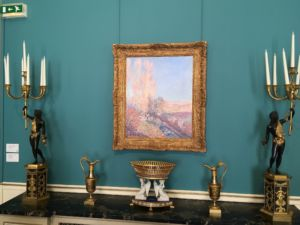 A Sisley painting above some ornate candelabras and pitchers.
