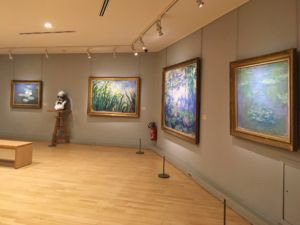 Four of Monet's water lilly paintings and a bust of the painter.